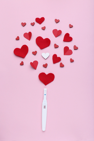 Pregnancy test with paper red hearts on pink background