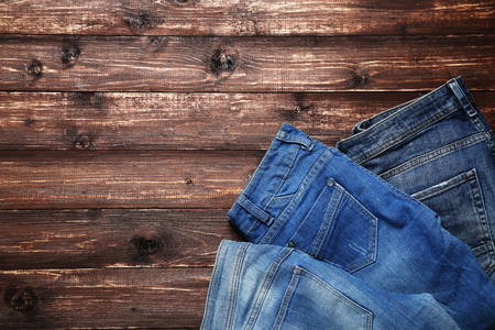 Folded jeans on brown wooden table Stock Photo