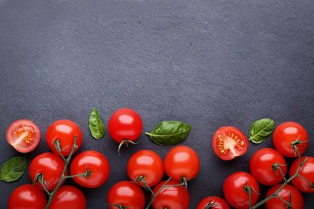 Pomidory czereśniowe z listkami bazylii na czarnym tle