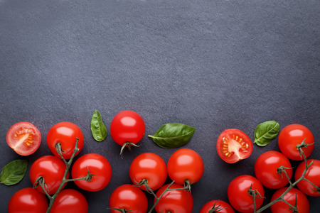 Cherry tomatoes with basil leafs on black background
