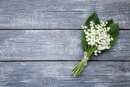 Lily of the valley flowers on grey wooden table
