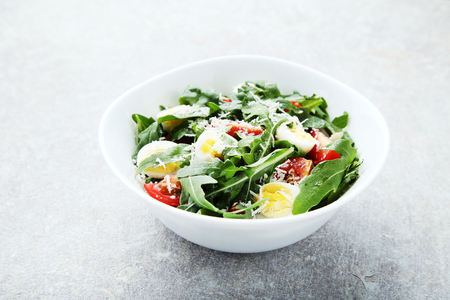 Salad with arugula leafs, tomatoes and eggs on grey wooden table