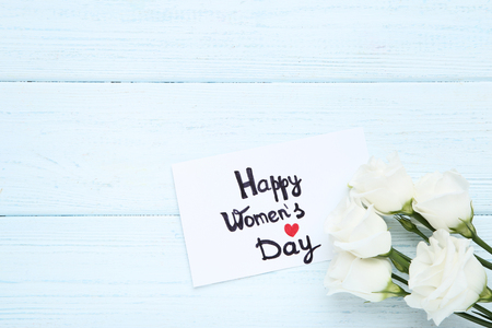 Text Happy Women's Day with eustoma flowers on wooden table