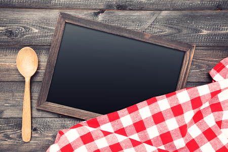 Blank chalkboard with red napkin and spoon on wooden background Stockfoto