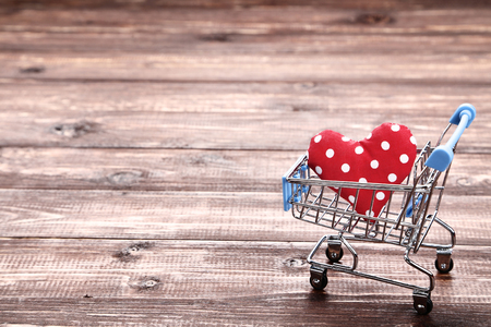 Shopping cart with red fabric heart on brown wooden table