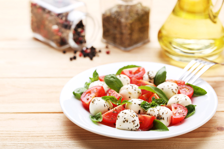Mozzarella, tomatoes and basil leafs on brown wooden table