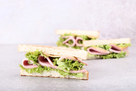 Sandwiches with ham, cheese and vegetables on grey background