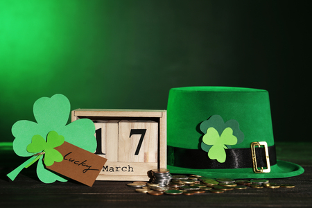 Clover leafs with wooden calendar, green hat and coins Stock Photo - 116600248