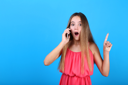 Emotional girl talking on a mobile phone on blue background 写真素材