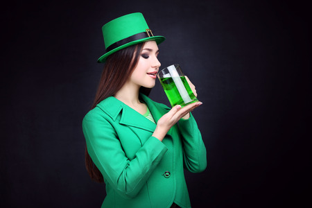 St. Patricks Day. Beautiful woman wearing green hat and drinking beer 写真素材