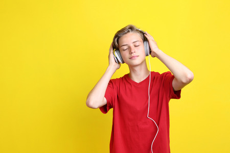 Cute teenager with headphones on yellow background Imagens