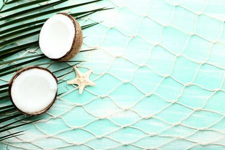 Coconuts with palm leaf and starfish on wooden table Foto de archivo