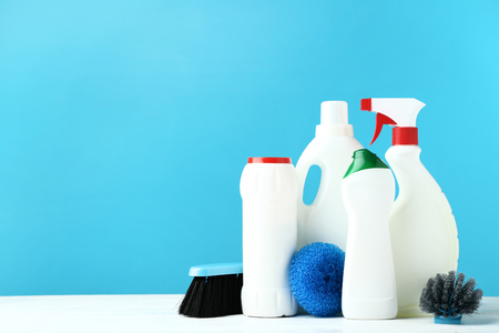 Bottles with detergent and cleaning tools on wooden table Stok Fotoğraf - 117070362