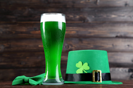 St. Patricks Day. Glass of green beer with bow tie and hat on wooden background Stock Photo