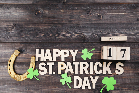 Golden horseshoe with clover leafs, wooden calendar and text Happy St.Patrick's Day Stock Photo