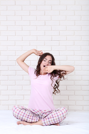 Yawning girl in pajamas sitting on white bed Stockfoto