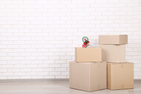 Cardboard boxes with dispenser on brick wall background