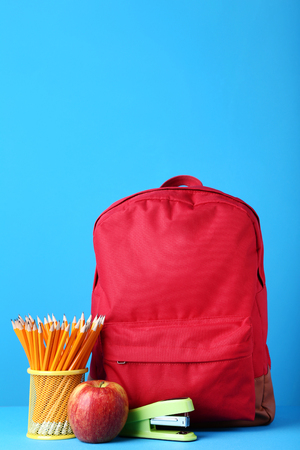 Red backpack with school supplies on blue background Stock Photo