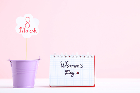 Text Women's Day in notepad with bucket on pink background