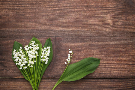 Lily of the valley flowers on brown wooden table Фото со стока
