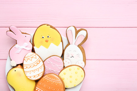 Easter gingerbread cookies in plate on pink wooden table