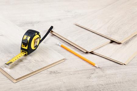 Holzlaminatboden mit Bleistift und Maßband Standard-Bild