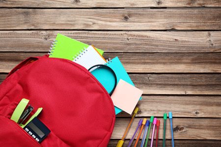 Red backpack with school supplies on brown wooden table