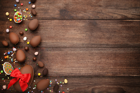 Chocolate easter eggs with colorful candies on brown wooden table