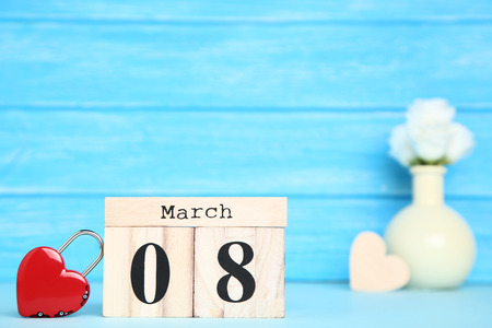 Women's Day on wooden calendar with heart shaped padlock on blue background Imagens