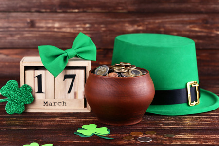 St. Patricks Day. Green hat with clover leafs, wooden calendar and coins