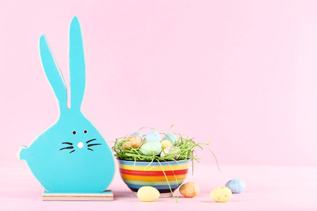 Wooden rabbit with easter eggs on pink background