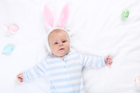 Baby boy in rabbit ears lying on white bed