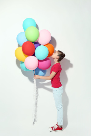 Beautiful young girl with colored balloons on white background Stock Photo