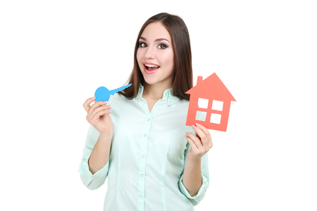 Young woman showing paper house and keys on white background