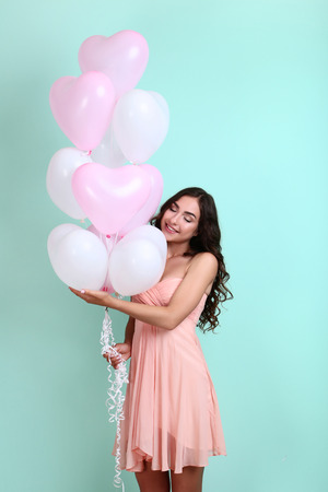 Young girl with pink and white balloons on mint background