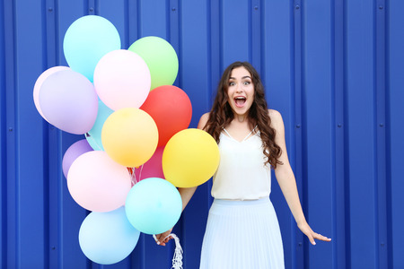 Happy girl with colored balloons on blue background