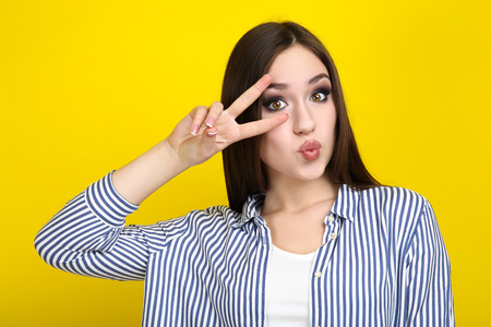 Beautiful young woman on yellow background