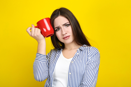 Beautiful young woman with red cup on yellow background Stock Photo