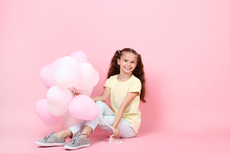 Cute young girl with balloons sitting on pink background Stock Photo