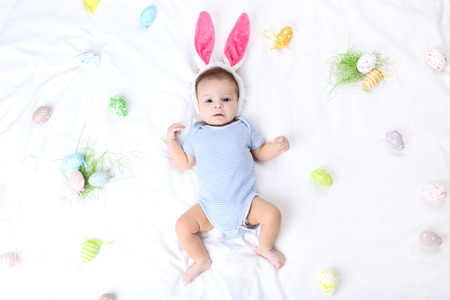 Cute baby with easter eggs and rabbit ears lying on white bed