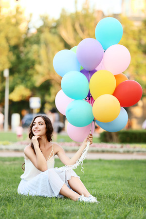 Beautiful girl with colored balloons sitting on green grass Stock Photo