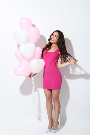 Beautiful girl with heart balloons on white background