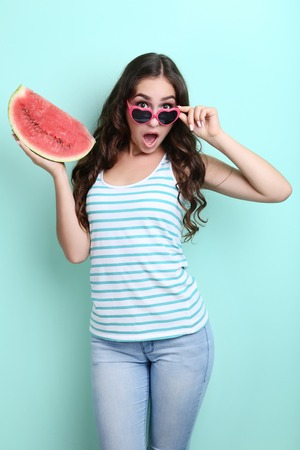 Beautiful woman in sunglasses holding watermelon on mint background