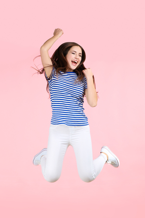 Jumping beautiful girl on pink background