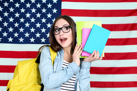 Young student with backpack and books on American flag background