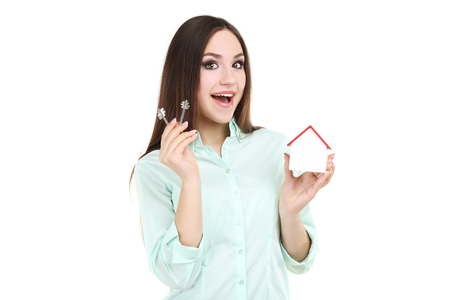 Young woman showing keys and wooden house on white background