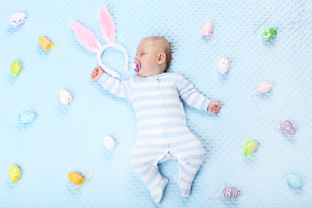 Baby boy with easter eggs lying on bed