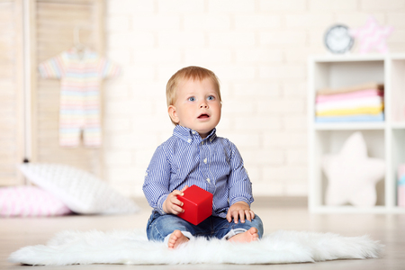 Baby boy with toy cube sitting at home Stock Photo