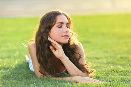 Young woman lying on green grass in the park