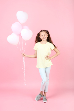 Cute young girl with balloons on pink background